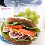 15555835-Healthy-lunchbox-with-wholemeal-ham-sandwich-fruit-yogurt-and-orange-juice--Stock-Photo